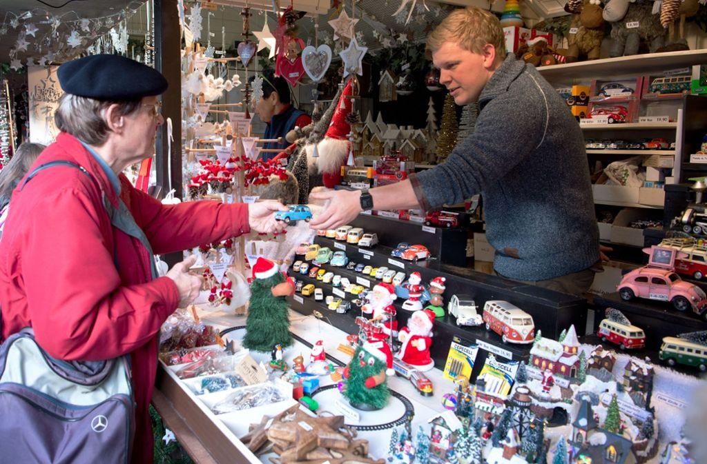 Kevin Maurer (rechts) hat seinen ersten Tag auf dem Weihnachtsmarkt. Die kleinen Blechautos locken jedes Jahr viele Stammkunden (links) an den Stand seiner Chefin. Foto: Oliver Willikonsky / Lichtgut