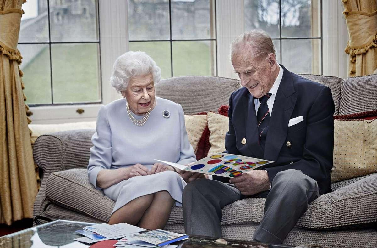 Die britische Königin Elizabeth II. und ihr Ehemann Prinz Philip, Herzog von Edinburgh, sitzen im Oak Room im Schloss Windsor. Sie sehen sich selbst gebastelte Hochzeitstagskarten an, die sie von ihren Großenkeln anlässlich ihres 73. Hochzeitstages geschenkt bekommen haben. Foto: dpa/Chris Jackson/Buckingham Palace/PA Media