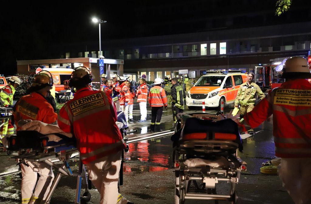Feuerwehrleute und eine Notärztin stehen nach einem Brand im Marien Hospital vor dem Krankenhaus um einen Patienten auf einer Liege herum. Bei dem Brand ist ein Mensch ums Leben gekommen, 72  weitere Patienten wurden verletzt. Foto: dpa