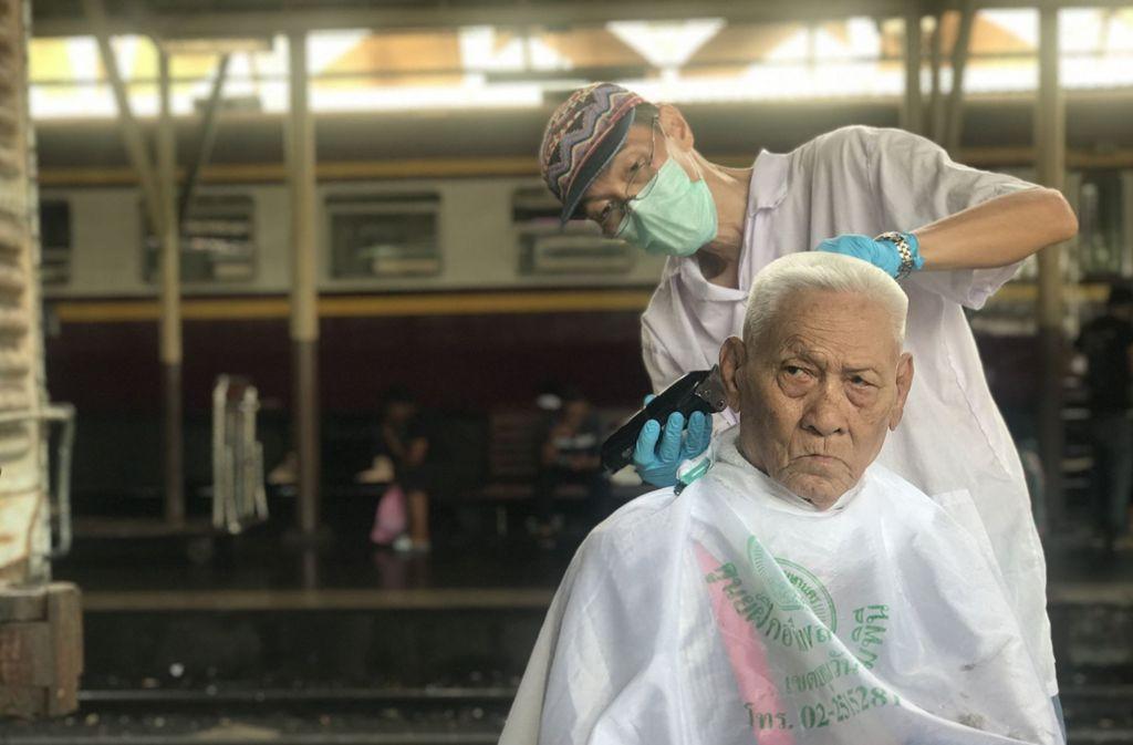 In Bangkok bekommen Bahnfahrer kostenlose Haarschnitte. Foto: dpa
