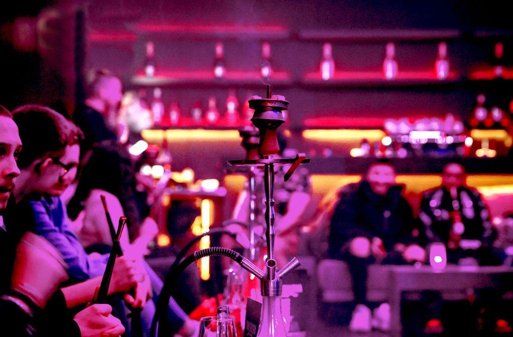 """Wenige Tage nach dem rassistischen Anschlag auf Shisha-Bars in Hanau rauchen Besucher im """"Nice-Club"""" an der Theodor-Heuss-Straße die Wasserpfeife. Foto: Lg/Rettig"""