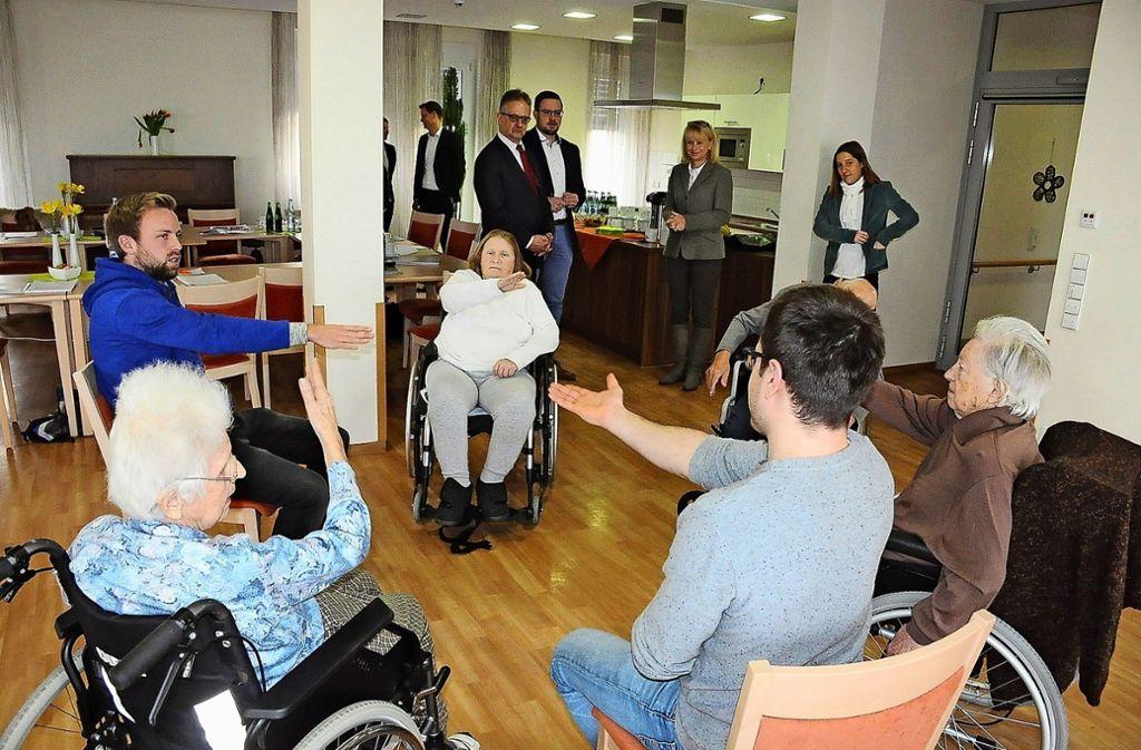 Pfleger zeigen mit einer Bewohnergruppe im Haus Martin Übungen zur Beweglichkeit. Foto: Georg Linsenmann