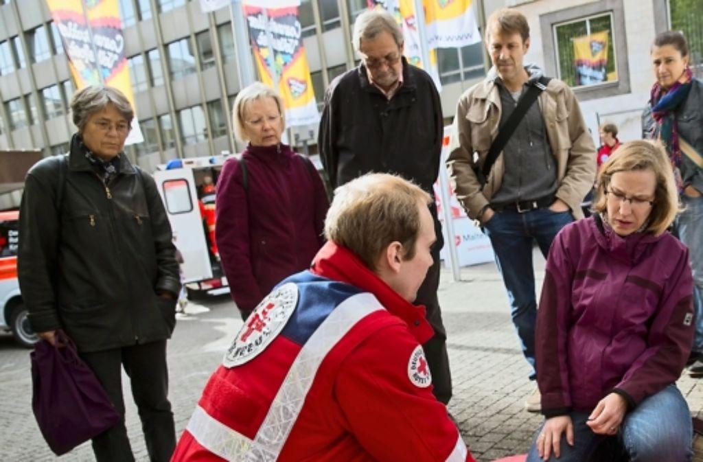 Der Rettungsassistent Simon Haase zeigt Passanten an einer Reanimationspuppe, was bei einem Notfall zu tun ist. Foto: Achim Zweygarth