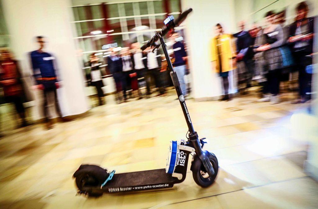 Ganz ohne Chauffeur rollert der E-Scooter der Uni Stuttgart durch das Foyer der Hochschule für Technik – und von Mitte nächsten Jahres an auch auf dem Campus in Stuttgart-Vaihingen. Nach dem Transport fährt er allein zum Standort zurück. Foto: Lg/Christoph Schmidt