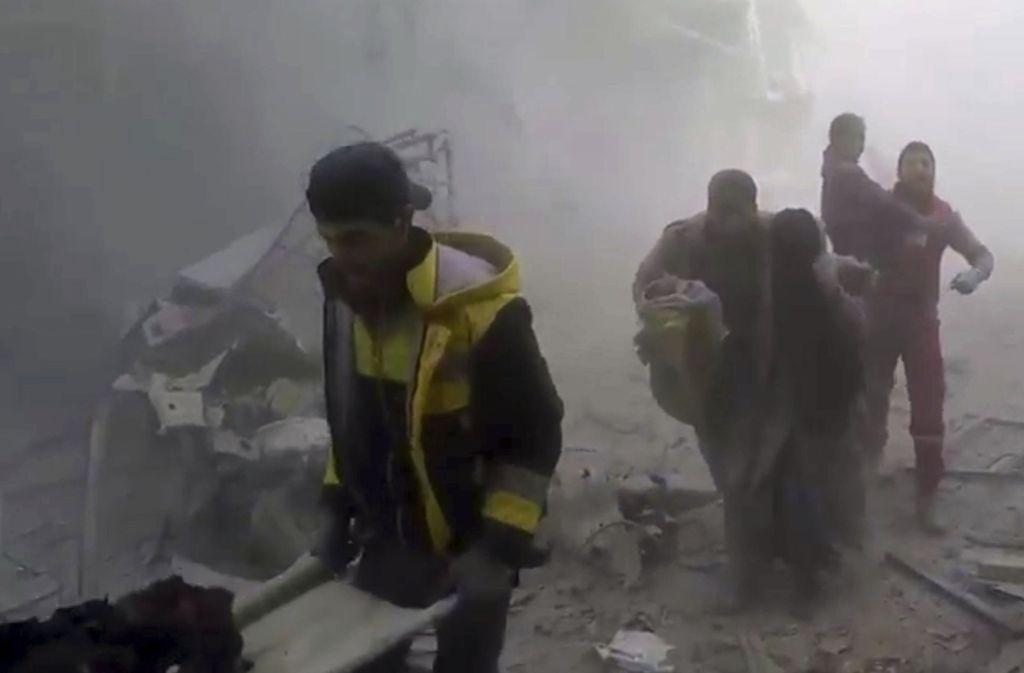 """Das von  Syrischen """"Weißhelmen"""" zur Verfügung gestellte Videostandbild zeigt Mitglieder des Zivilschutzes, die während Luftangriffen und Beschuss Anwohnern  von Ost-Ghuta helfen. Foto: dpa"""