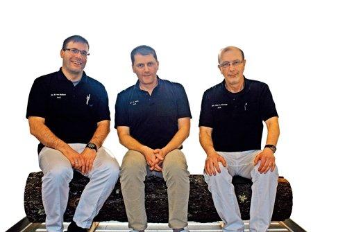 Ein Schwarzwälder Baumstamm als origineller Sitzplatz in der Regiopraxis in Baiersbronn, drei Ärzte haben Platz genommen: (von links) Wolfgang von Meißner, Michael Seitz und Ernst Klumpp. Foto: Koch-Widmann