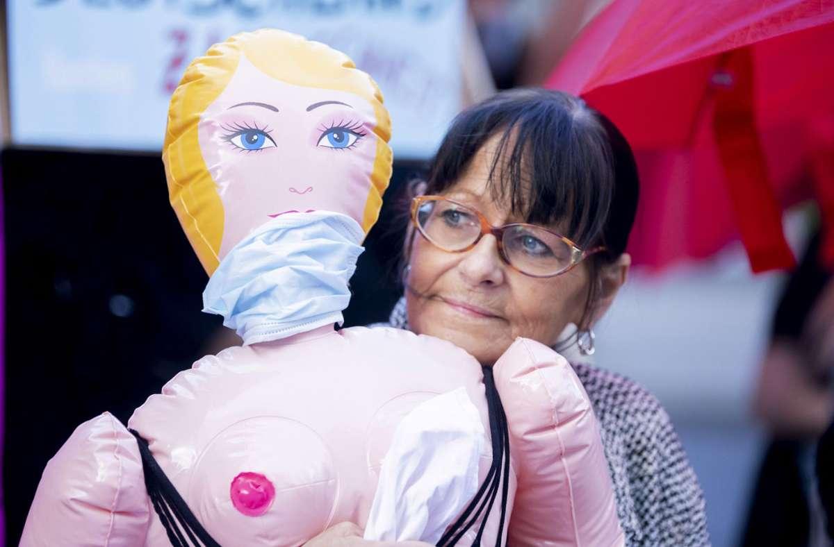 Eine Teilnehmerin steht bei einer Protestaktion für die Öffnung von Prostitutionsstätten mit einer Sexpuppe im Arm nahe des Bundesrates. Foto: dpa/Christoph Soeder