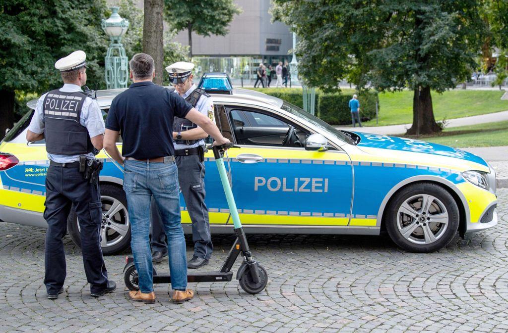 Verkehrskontrolle in  Stuttgart: Ein E-Scooter Fahrer wird von der Polizei verwarnt, weil er über einen Fußgängerweg gefahren ist. Foto: dpa