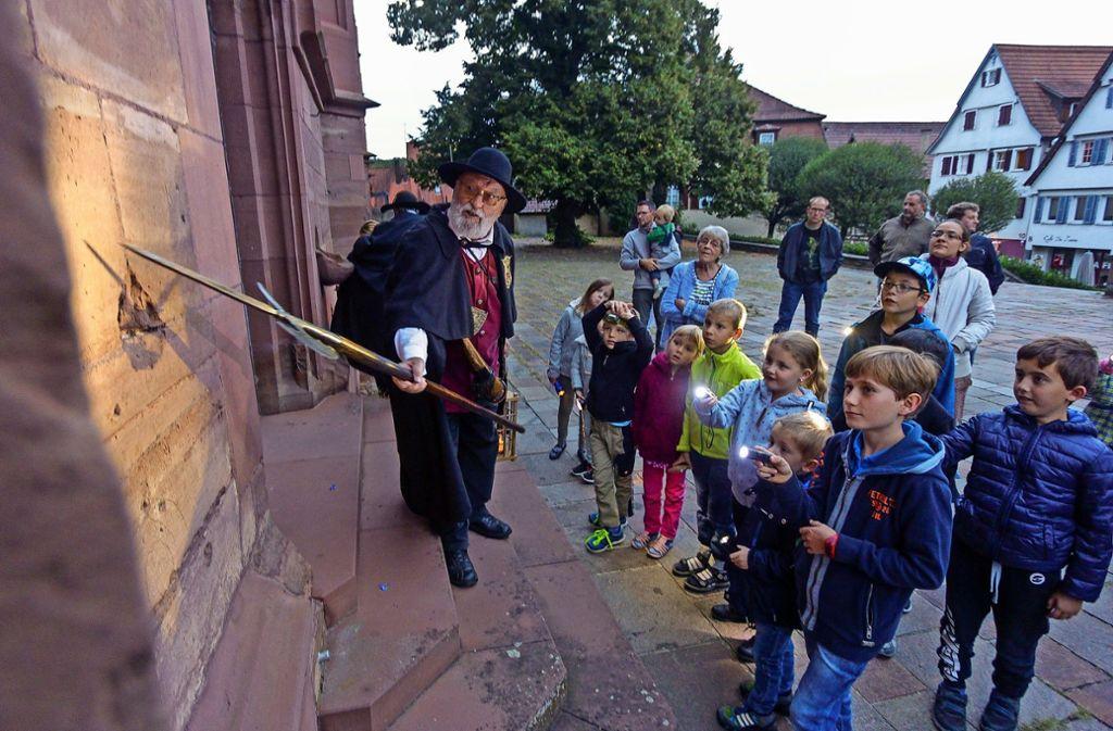 Nachtwächter Gerd Diebold erklärt den Kindern die katholische Stadtkirche. Foto: factum/Bach