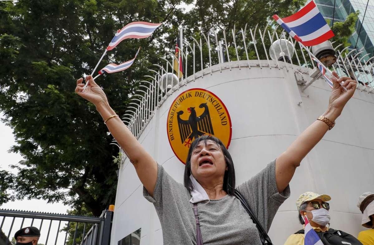 Eine Unterstützerin der thailändischen Monarchie schwenkt Nationalfähnchen vor der deutschen Botschaft. Foto: dpa/Gemunu Amarasinghe