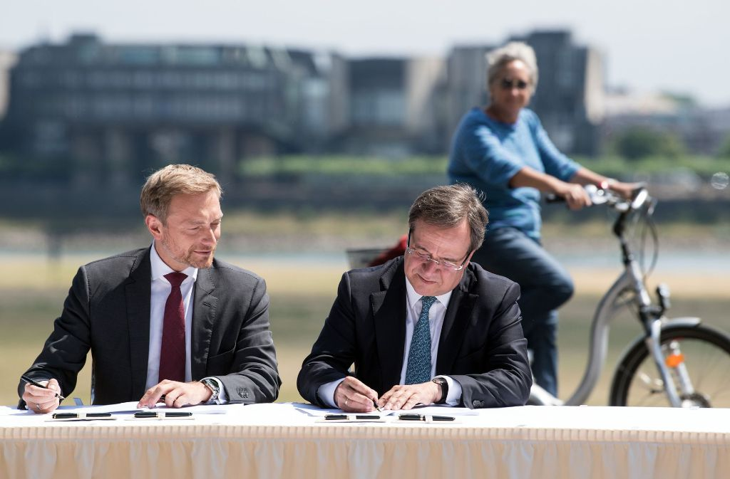 Politidylle: Christian Lindner (FDP/links) und Armin Laschet (CDU) unterzeichnen unter den Augen einer interessierten Bürgerin den Koalitionsvertrag. Foto: dpa