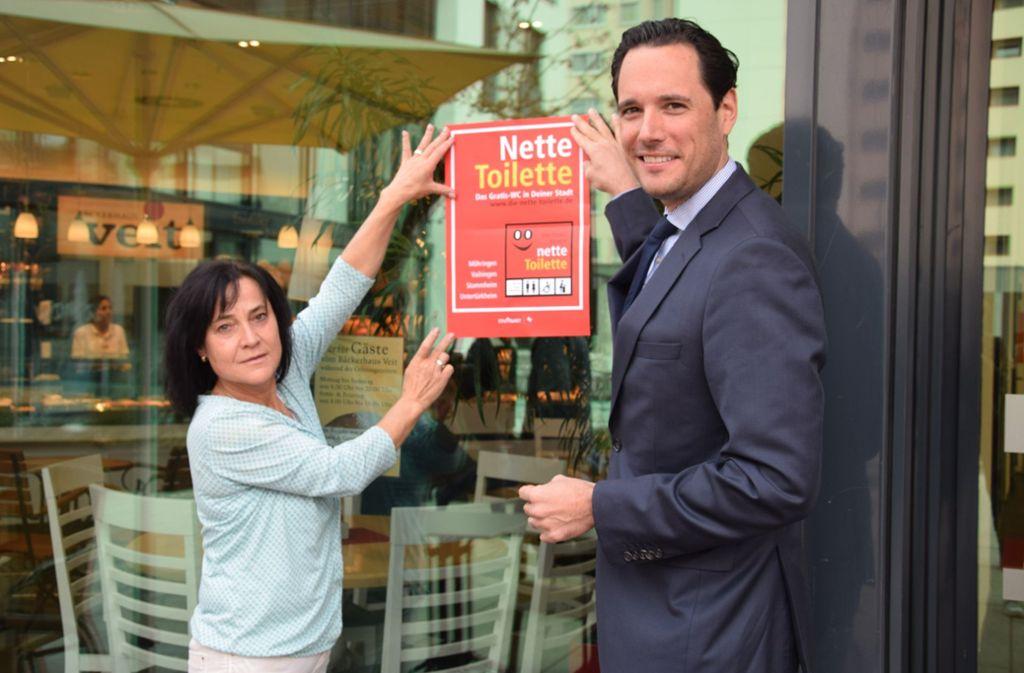 Bärbel Meizler, Bezirksleiterin bei der Bäckerei Veit, und Verwaltungsbürgermeister Fabian Mayer haben das erste Nette-Toilette-Schild aufgehängt. Foto: Alexandra Kratz