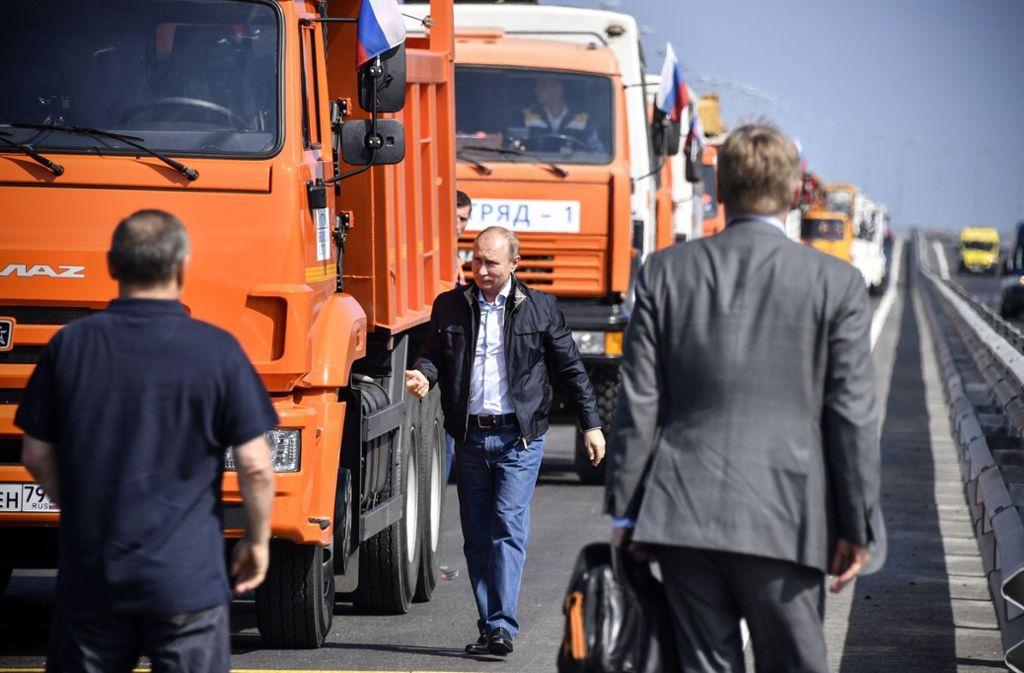 Wladimir Putin besteigt den ersten LKW in einem Tross von Baumaschinen. Für den russischen Präsidenten eine gute Gelegenheit, sich als Macher feiern zu lassen.  Foto: AFP