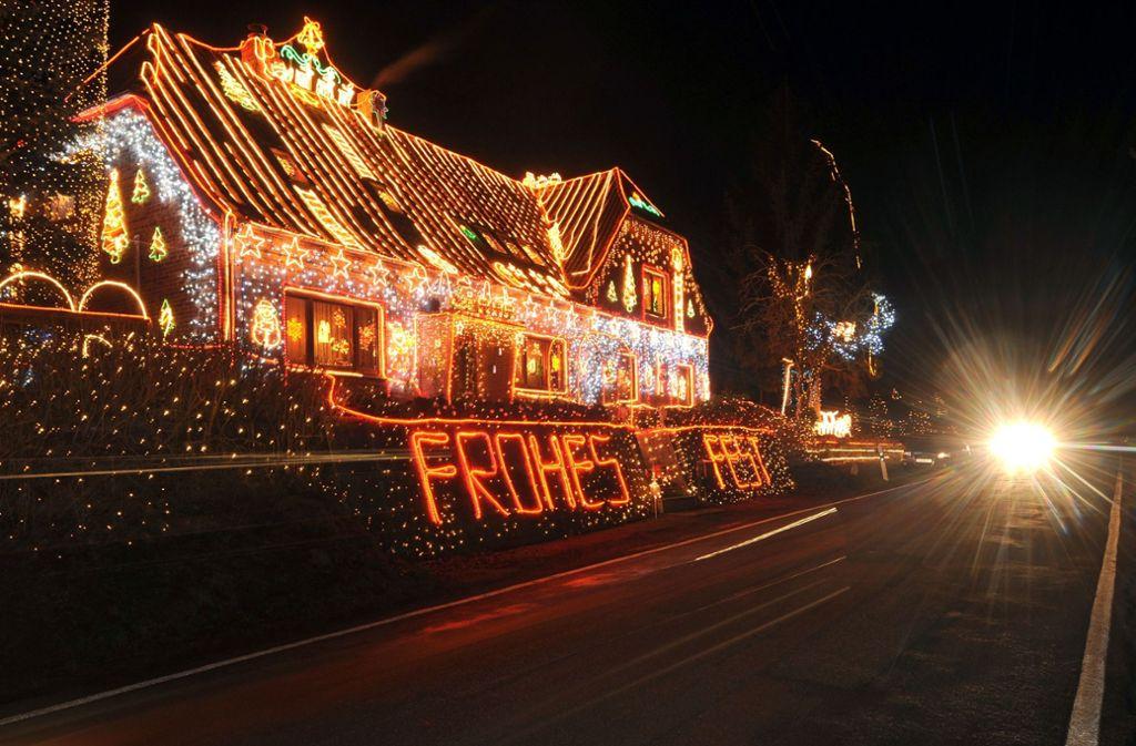 Ein Auto fährt an einem üppiger Weihnachtsbeleuchtung erstrahlten Wohnhaus in Calle bei Bücken (Kreis Nienburg) vorbei. Foto: dpa