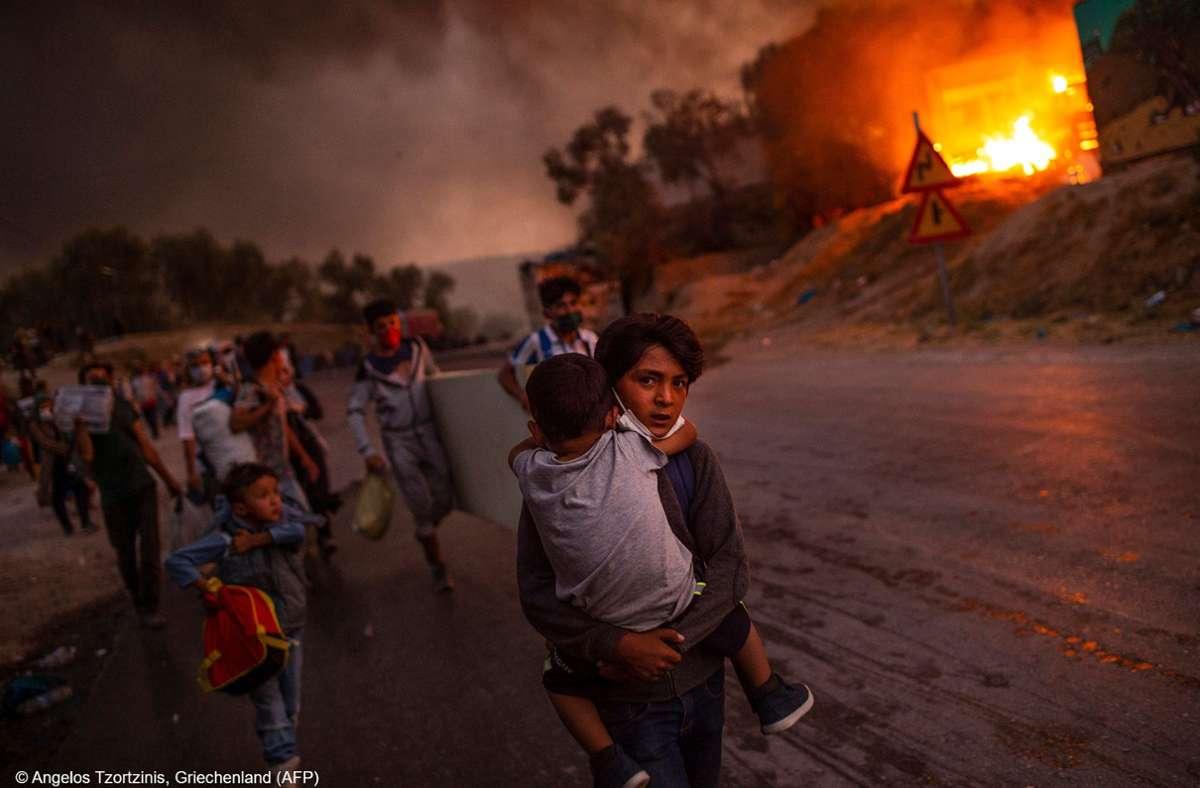 Das «Unicef-Foto des Jahres 2019» zeigt Kinder, die aus dem brennenden Flüchtlingslager Moria auf der griechischen Insel Lesbos fliehen. Foto: dpa/Angelos Tzortzinis, Griechenland
