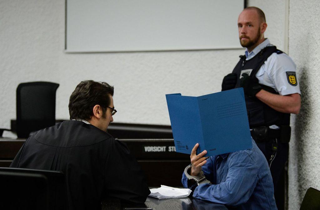 Der Angeklagte (links sein Verteidiger Nenad Mikec) verbirgt sein Gesicht. Foto: dpa