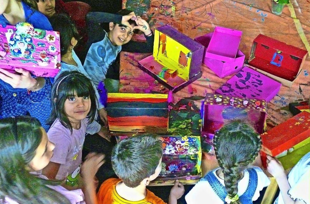 Um nicht gehen zu müssen, verstecken  sich die Kinder  in einem Welthaus, dass sie aus Kartons gebaut und gemeinsam bemalt haben. Foto: Petra Mostbacher-Dix