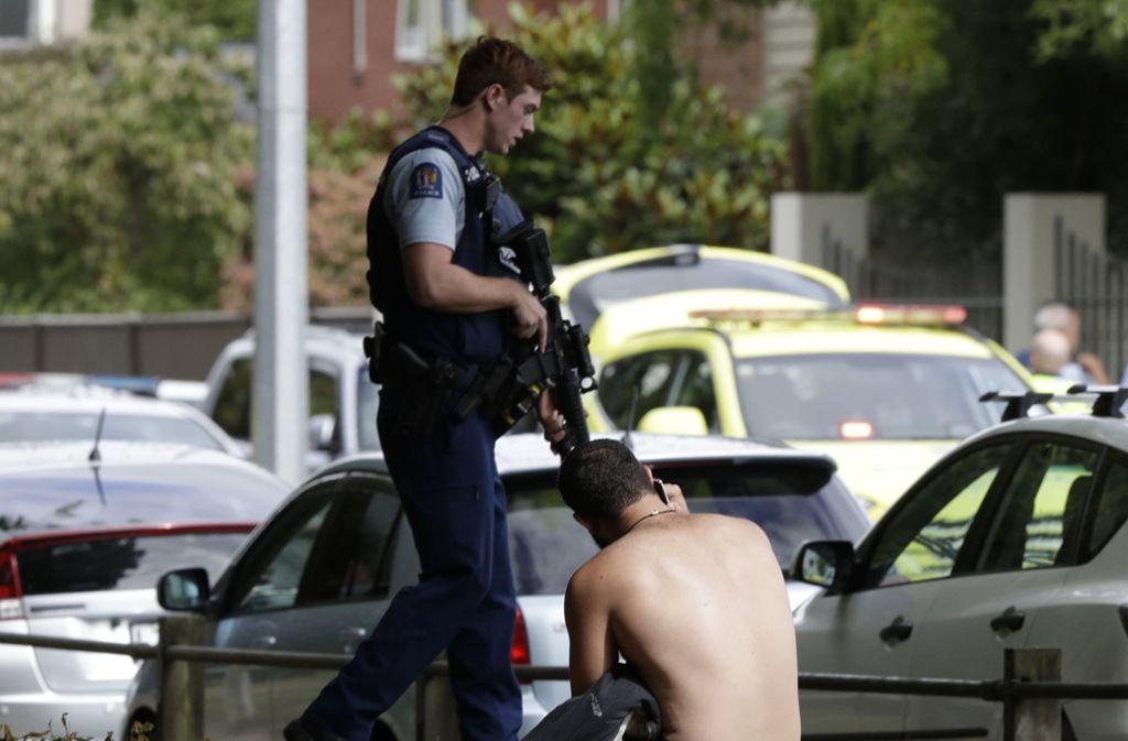 Ein Mann sitzt telefonierend am Boden. Vor ihm ein schwer bewaffneter Polizist. Foto: AP