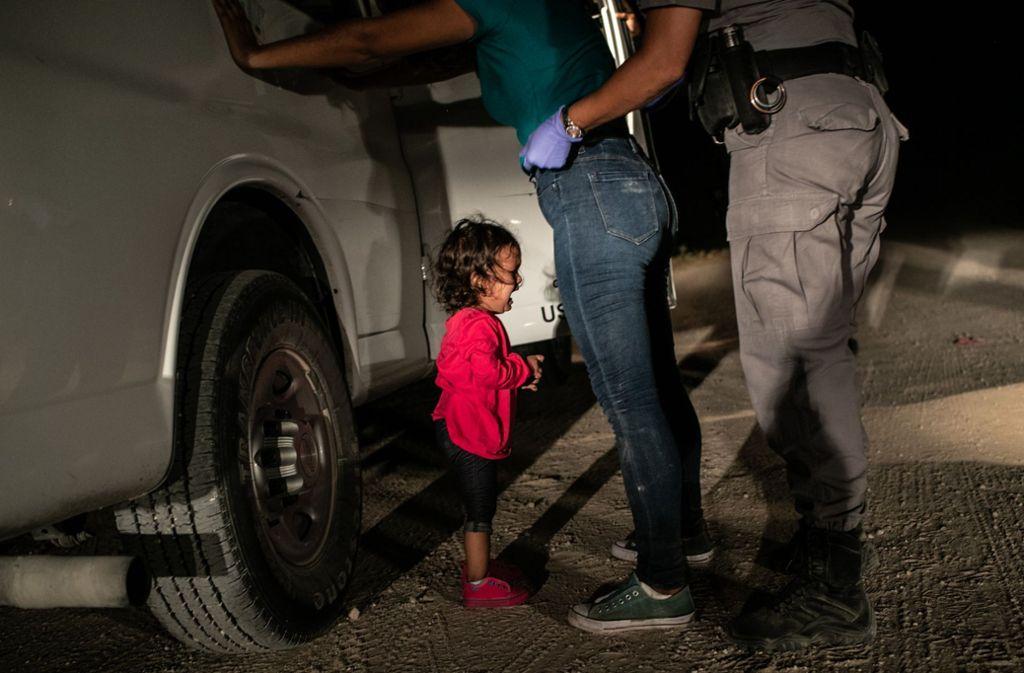 Das Pressefoto des Jahres zeigt das Flüchtlingsmädchen Yanela Sanchez, weinend an der US-mexikanischen Grenze. Ihre Mutter, die Honduranerin Sandra Sanchez steht vor ihr und wird von einem Grenzschutzbeamten abgetastet. Foto: John Moore/Getty Images/dpa