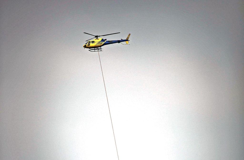 Mit einem Stahlseil befördert ein Helikopter die gefällten Bäume ab. Foto: Gottfried Stoppel
