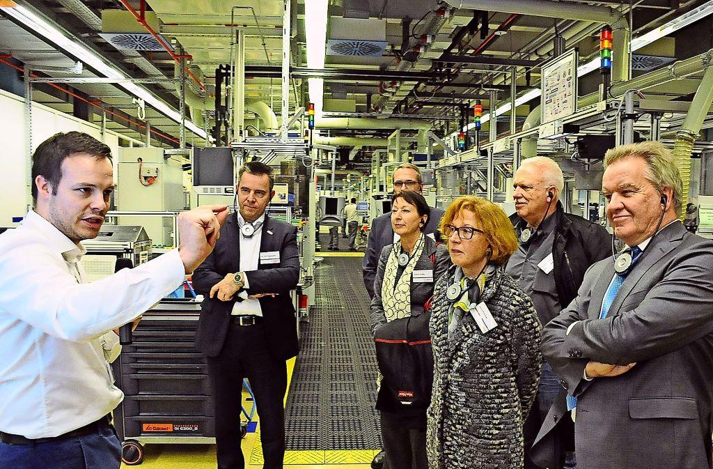 Bosch-Bereichsvorstand Uwe Gackstatter (2.v.l.),  Minister Franz Untersteller (r.) und die  weitere Gruppe im Gespräch mit einem Bosch-Ingenieur. Foto: Georg Linsenmann