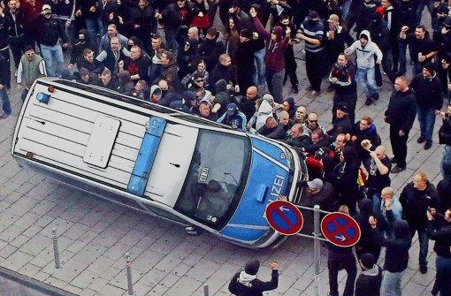 Demonstranten werfen  ein Polizeiauto um: mehrere Tausend  Hooligans aus dem gesamten Bundesgebiet randalierten am Sonntag in Köln. Foto: dpa