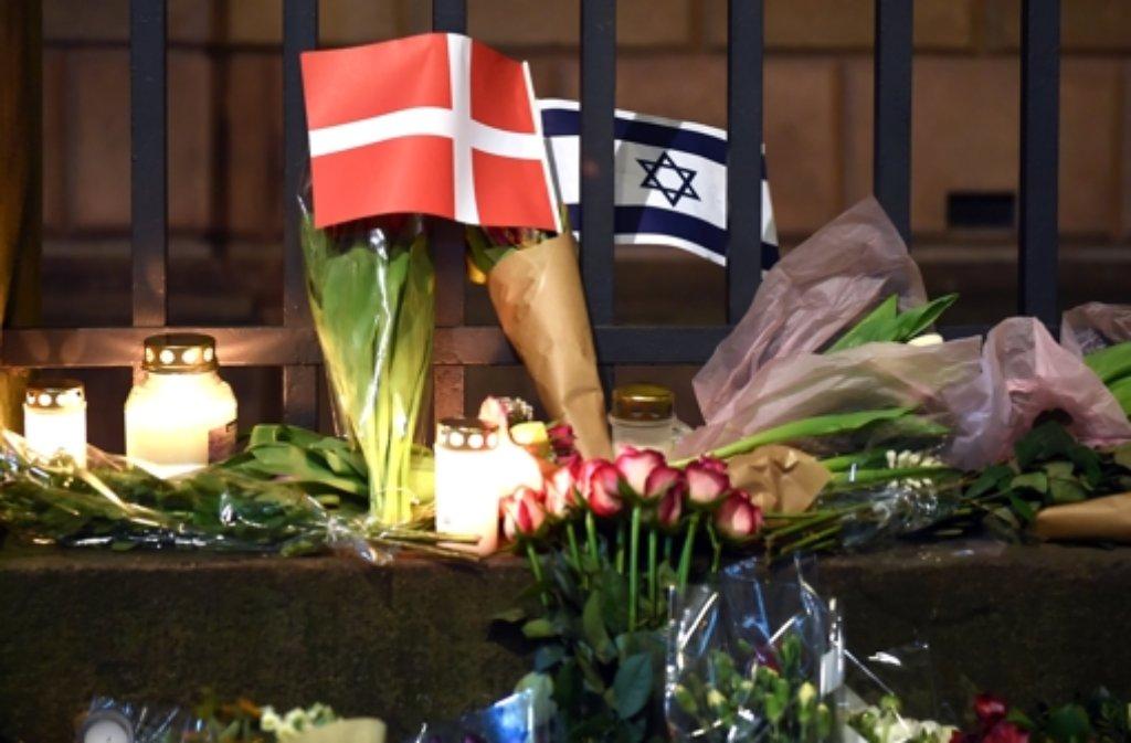 Trauernde haben Blumen und Kerzen an der Synagoge in der Kopenhagener Innenstadt niedergelegt. Ein 22-Jähriger soll dort einen 37 Jahre alten Wachmann erschossen haben. Foto: dpa