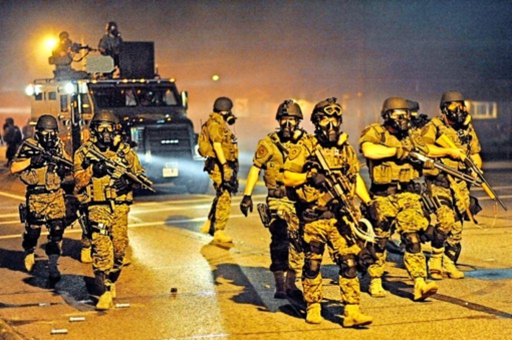 Wie eine Invasionsarmee: Polizisten mit Panzerwagen und Gewehren patrouillieren durch die Straßen von Ferguson. Foto: AFP, AP