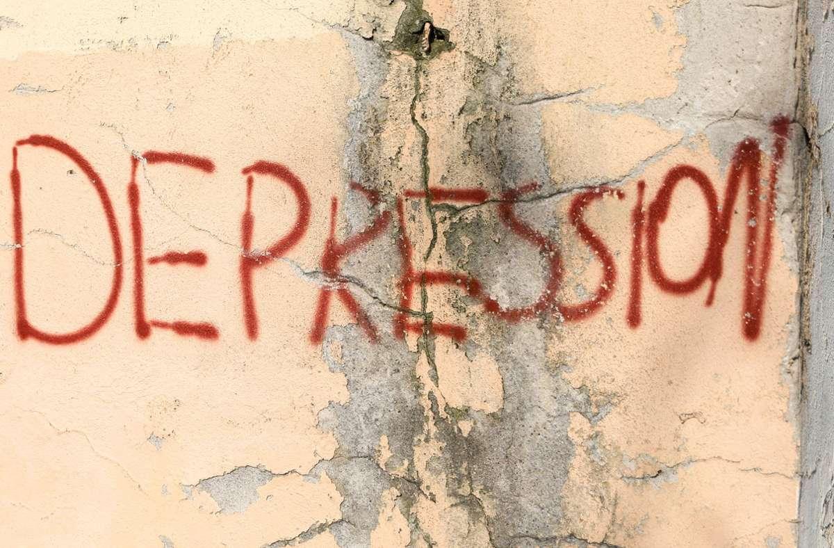 """Der  Schriftzug """"Depression"""" prangt an einer Hauswand. Foto: Jan Woitas/dpa"""