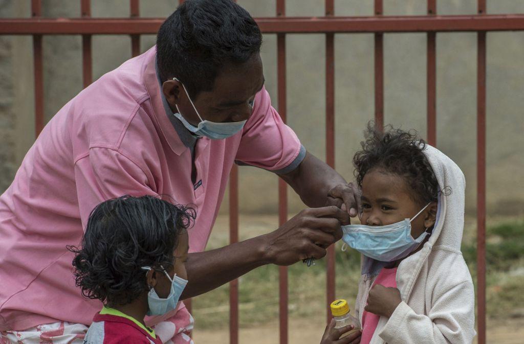 Rückkehr der Pest: 2017 breitete sich in Madagaskar die lebensgefährliche Lungenpest wieder aus. Auf dem Foto ist ein Helfer zu sehen, der Stadt  Antananarivo  einem Kind  einen Mundschutz anlegt. Foto: dpa/Alexander Joe