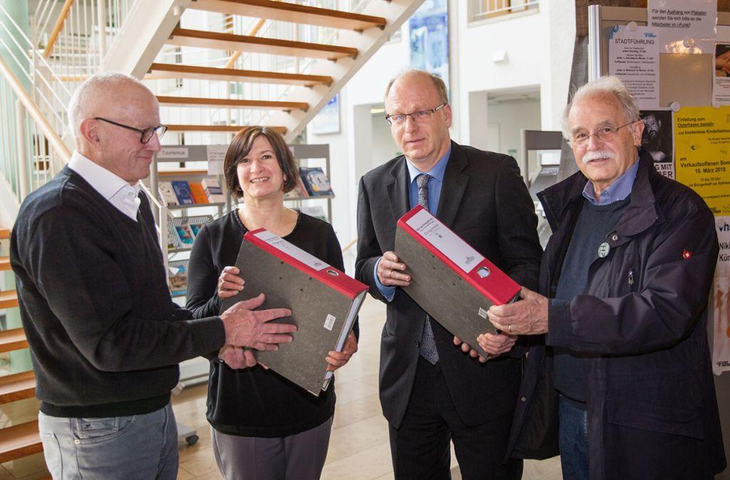 Fritz Eisele (links) und Dieter Braunmüller (rechts) übergeben im März 2018 im Nürtinger Rathaus Unterschriften gegen das geplante Hotel am Neckar. Foto: Ines Rudel