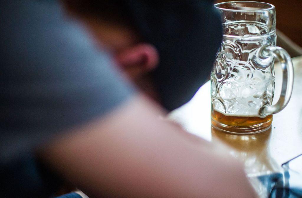 Ein Mann schläft in einer Gastwirtschaft vor einem fast leeren Maßkrug. Wer an den Karnevalstagen ein paar Gläser mehr trinkt, könnte einen ungebetenen Gast bemerken: den Kater nach dem Rausch. Foto: dpa