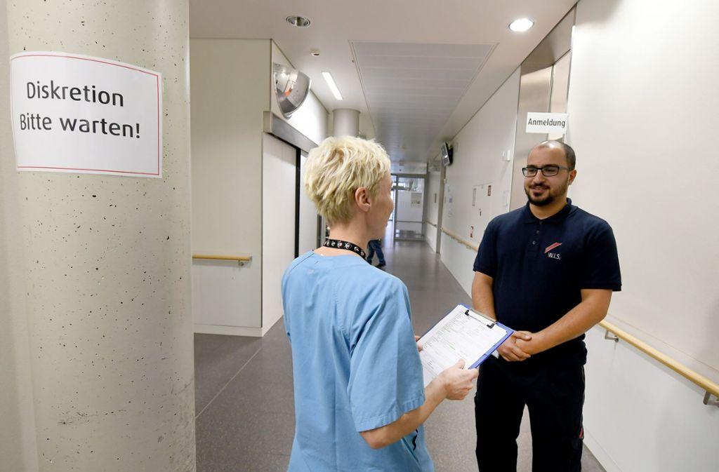 Lieber auf Nummer sicher: Wachmann im Gespräch mit einer Pflegekraft. Foto: dpa
