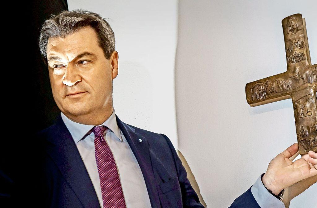 Markus Söder hängt ein Kreuz im Eingang der bayrischen Staatskanzlei auf. Foto: dpa