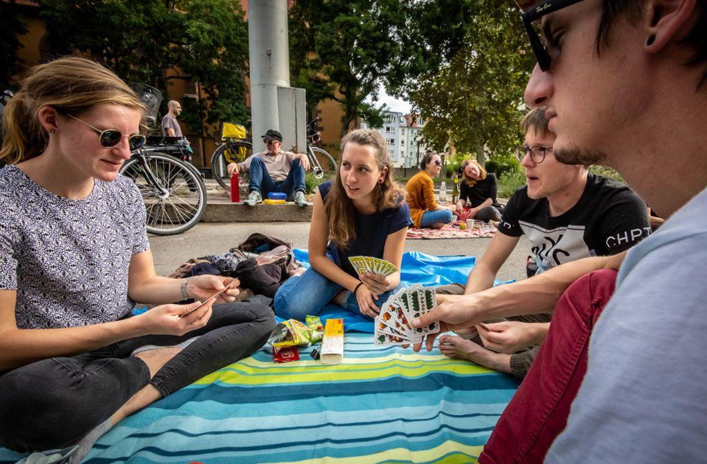 Mit der Picknickdecke auf der B14: Teilnehmer des Sit-Ins spielen Karten. Foto: Lichtgut/Julian Rettig/Julian Rettig