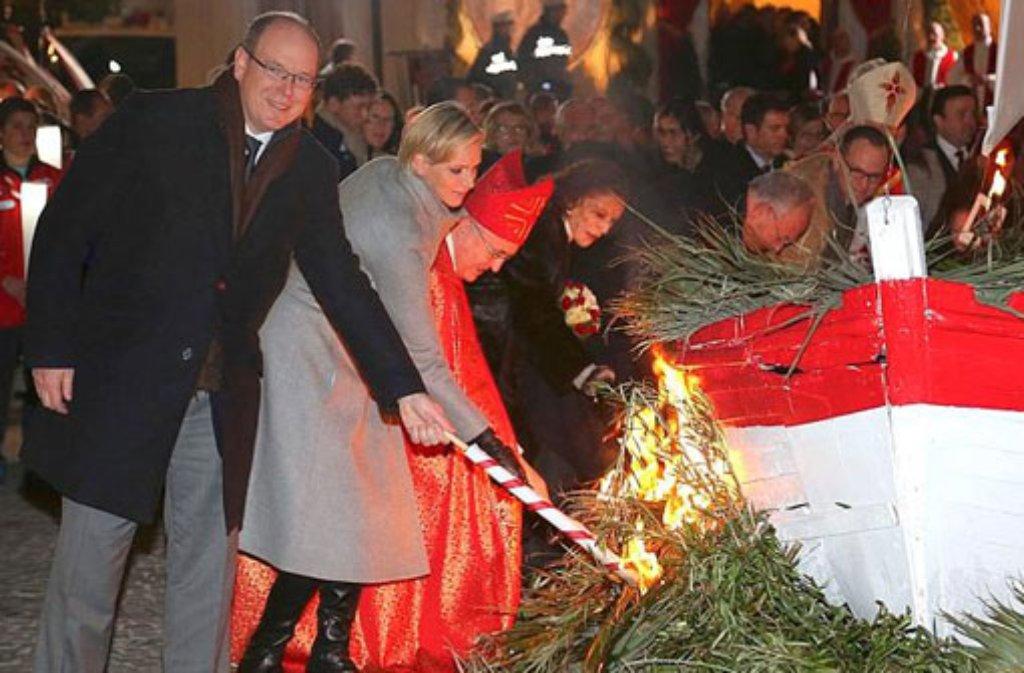 Fürstin Charlène von Monaco und ihr Mann Albert haben am Abend des 26. Januar zur Fackel gegriffen. Traditionell wird an diesem Datum an der Küste Monacos ein hölzernes Fischerboot verbrannt. Foto: dpa