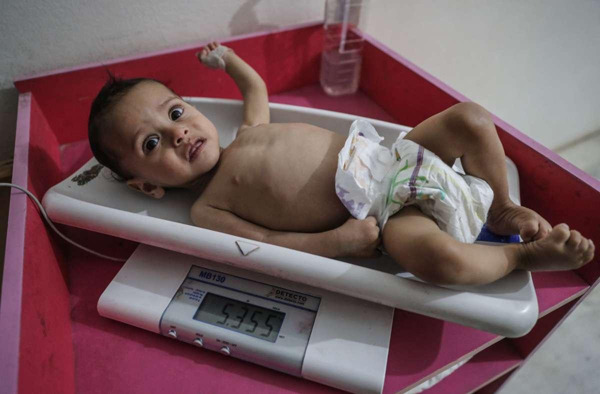 Eine Krankenschwester ermittelt das Gewicht eines unterernährten Kindes im Ibn Sina Krankenhaus im syrischen Idlib. Das Welternährungsprogramm (WFP) geht von 270 Millionen Menschen aus, die in 2021 akut an Hunger leiden oder davon stark gefährdet sein werden. Foto: Anas Alkharboutli/dpa