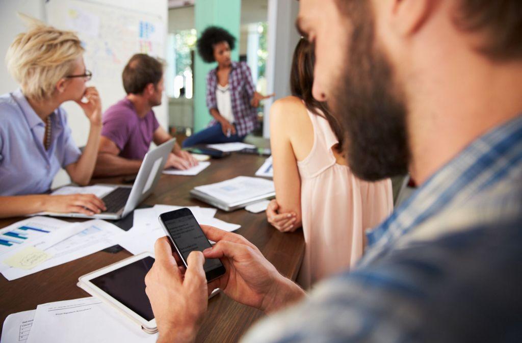 Verbreitete Unsitte: sich während eines Meetings mit dem Smartphone beschäftigen. Foto: Monkey Business/Adobestock