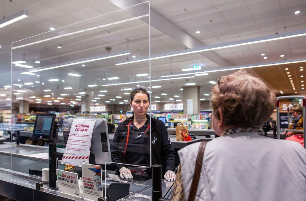 Eine Kundin spricht im Kassenbereich eines Supermarktes mit einer Kassiererin, die hinter einer schützenden Plexiglasscheibe steht. Foto: dpa