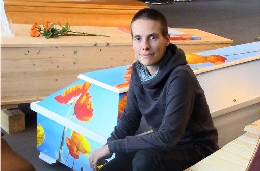Barbara Rolf kniet in der Niederlassung ihres Bestattungsinstituts zwischen Särgen in allen erdenklichen Größen und in unterschiedlichen Farben. Foto: Cedric Behman