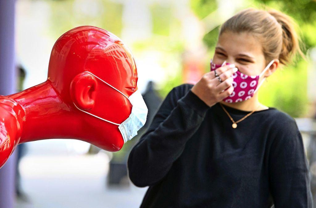 Mit einer Mundschutz tragenden Skulptur wirbt ein Geschäft in Osnabrück für den Verkauf von Mund-Nasen-Schutzmasken – sehr  zur Belustigung der Passanten. Foto: dpa/Friso Gentsch