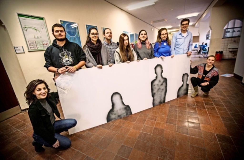 Die Recherchegruppe am Wagenburg-Gymnasium mit einer der plexiglasartigen Scheiben – die aufgesprühten Silhouetten symbolisieren die ehemaligen Schüler. Foto: Lichtgut/Piechowski