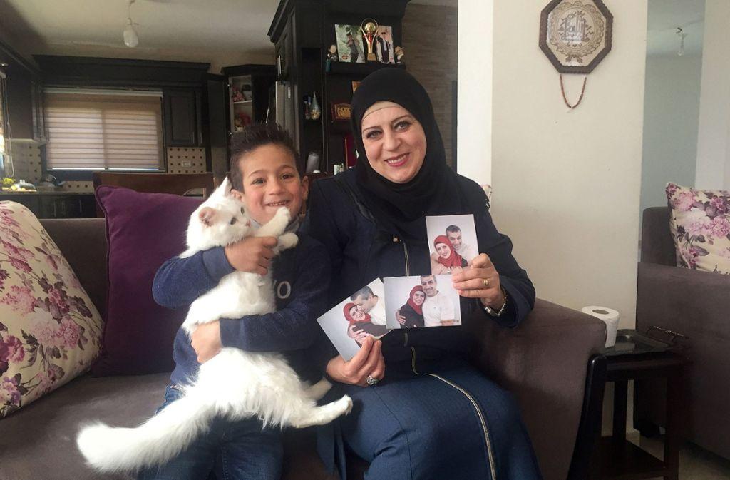 Sohn Madschd (5) und Lydia Rimawi (42) sitzen in ihrem Wohnzimmer auf dem Sofa. In ihren Händen hält Lydia Bilder von sich und ihrem Ehemann Foto: dpa