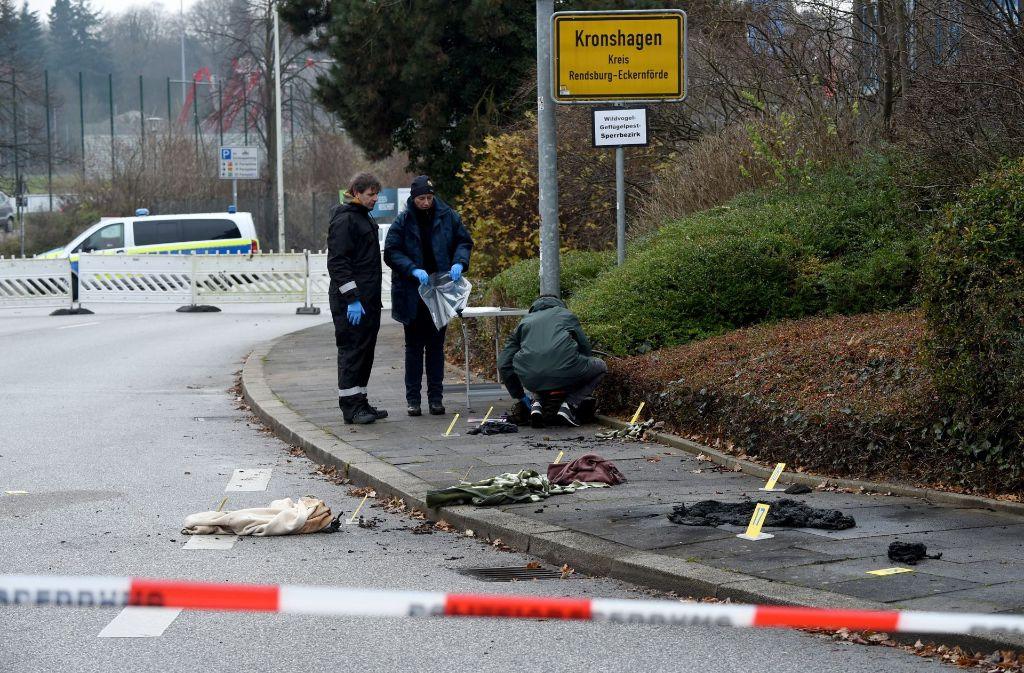 Kriminalbeamte sichern in Kronshagen bei Kiel (Schleswig-Holstein) am Tatort verbrannte Kleidungsstücke. Foto: dpa