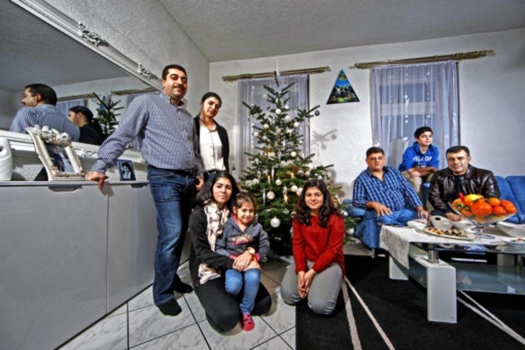 Weihnachten gibt es bei Jesiden nicht, einen Christbaum hat die Familie   dennoch:  Ahmed   Kurt (links)  mit seiner Frau, den vier Kindern und den Freunden Hassan Dnanie (auf dem Sofa links) und Khairi Blasini Foto: Gottfried Stoppel