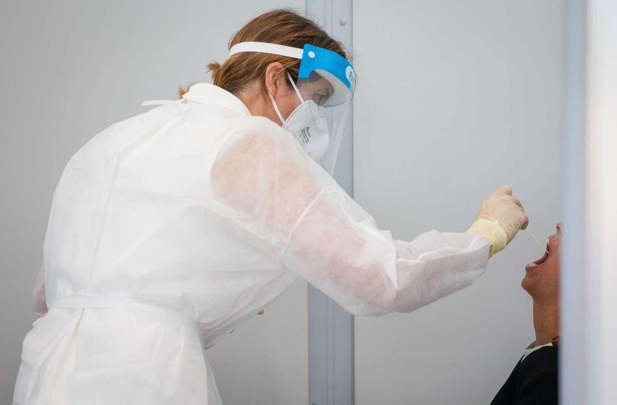 Eine Reisende wird im Corona-Testzentrum am Flughafen Stuttgart getestet. Foto: dpa/Christoph Schmidt