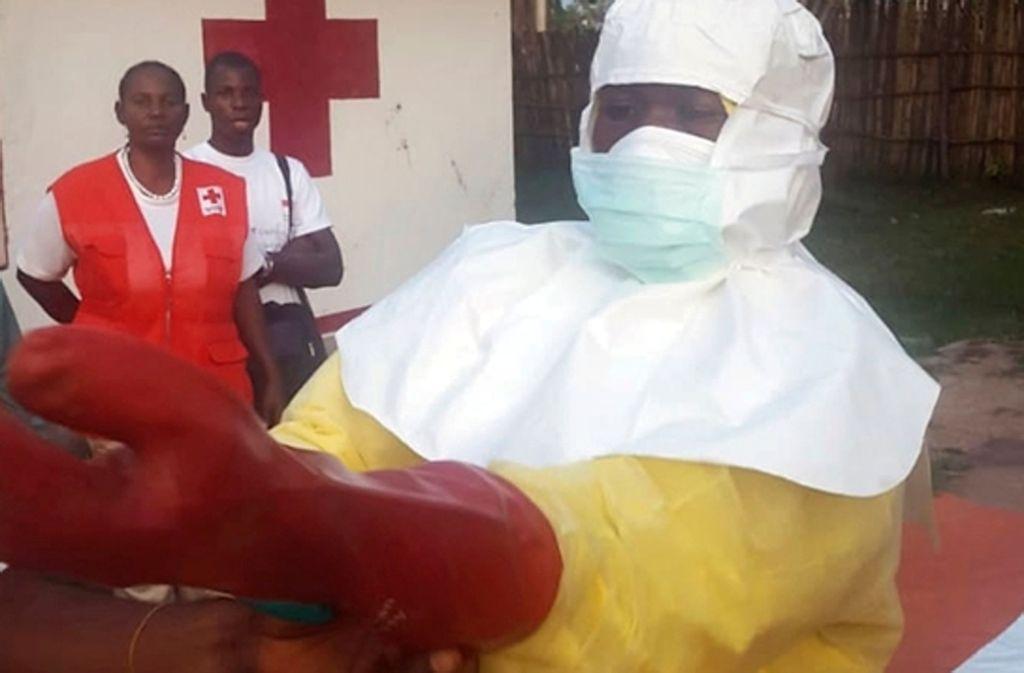 Ein Mitarbeiter vom Roten Kreuz zieht im Vorfeld der Suche nach Infizierten des Ebola-Virus Schutzkleidung an. Bis Freitag gingen die Behörden im Kongo von 45 möglichen Fällen aus. 25 Menschen sind bislang gestorben. Foto: dpa