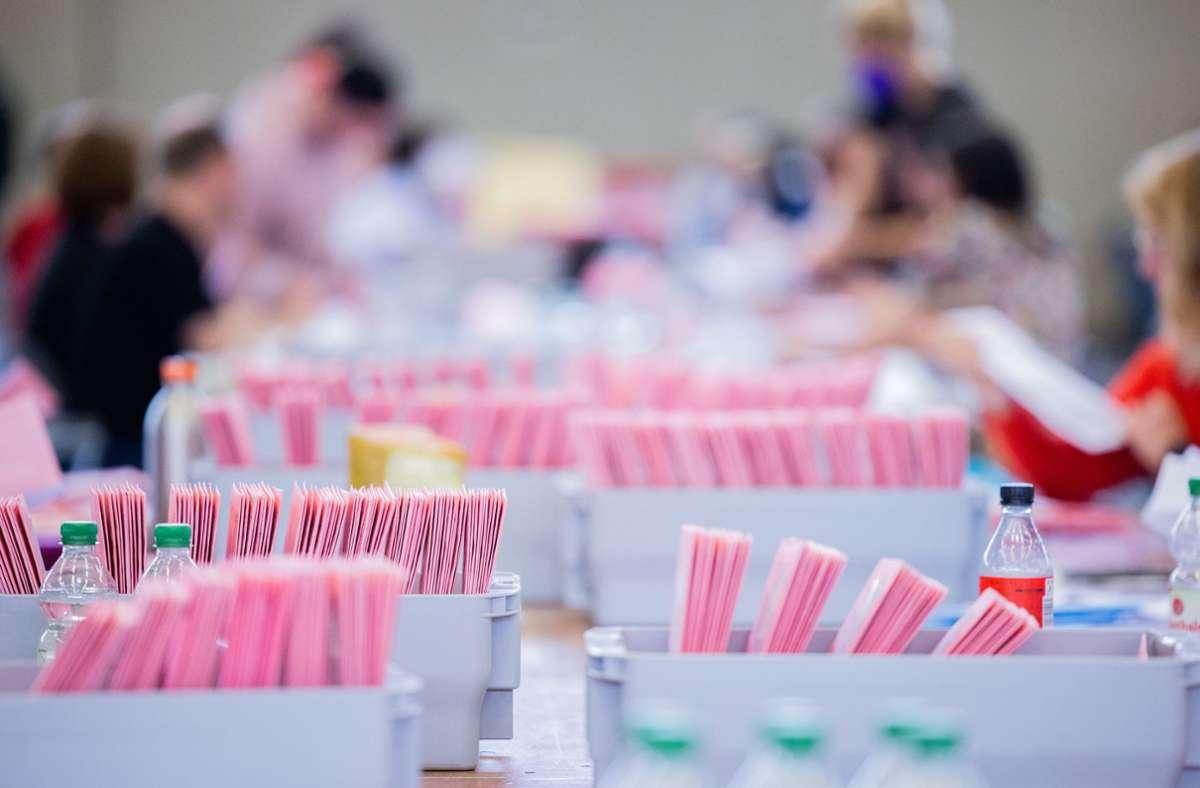 Wahlhelferinnen und Wahlhelfer öffnen bei der Auszählung der Briefwahl zur Bundestagswahl  die rosafarbenen Umschläge. Foto: dpa/Rolf Vennenbernd