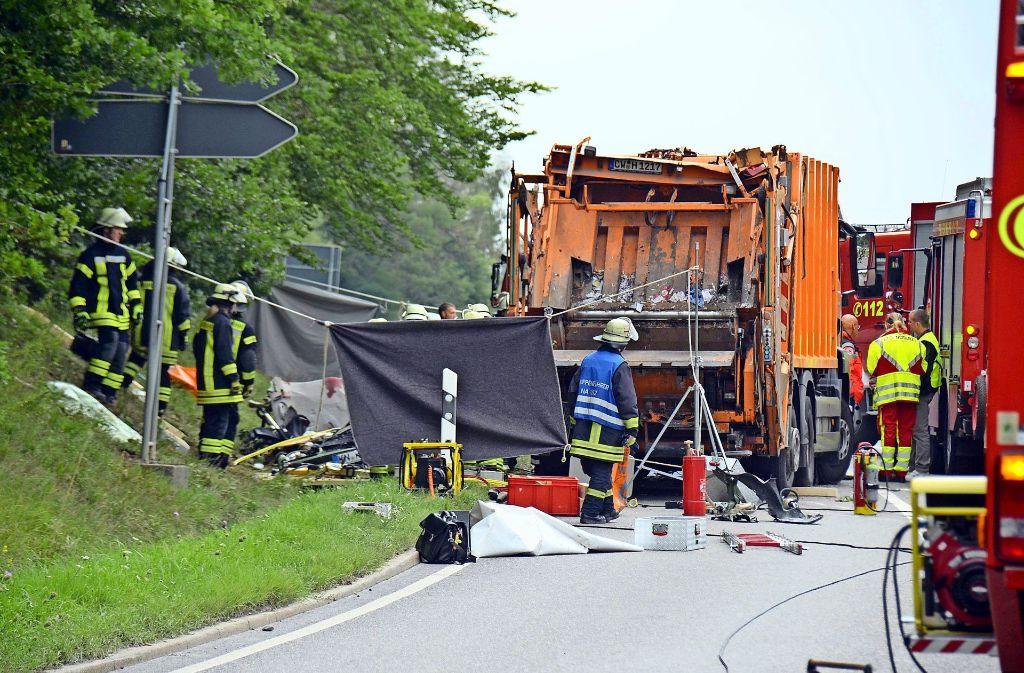 Die Feuerwehr hat die Unglücksstelle bei Nagold mit einem Sichtschutz verhängt. Beim Abbiegen fiel der Mülllaster auf ein Auto. Fünf Menschen starben. Foto: dpa