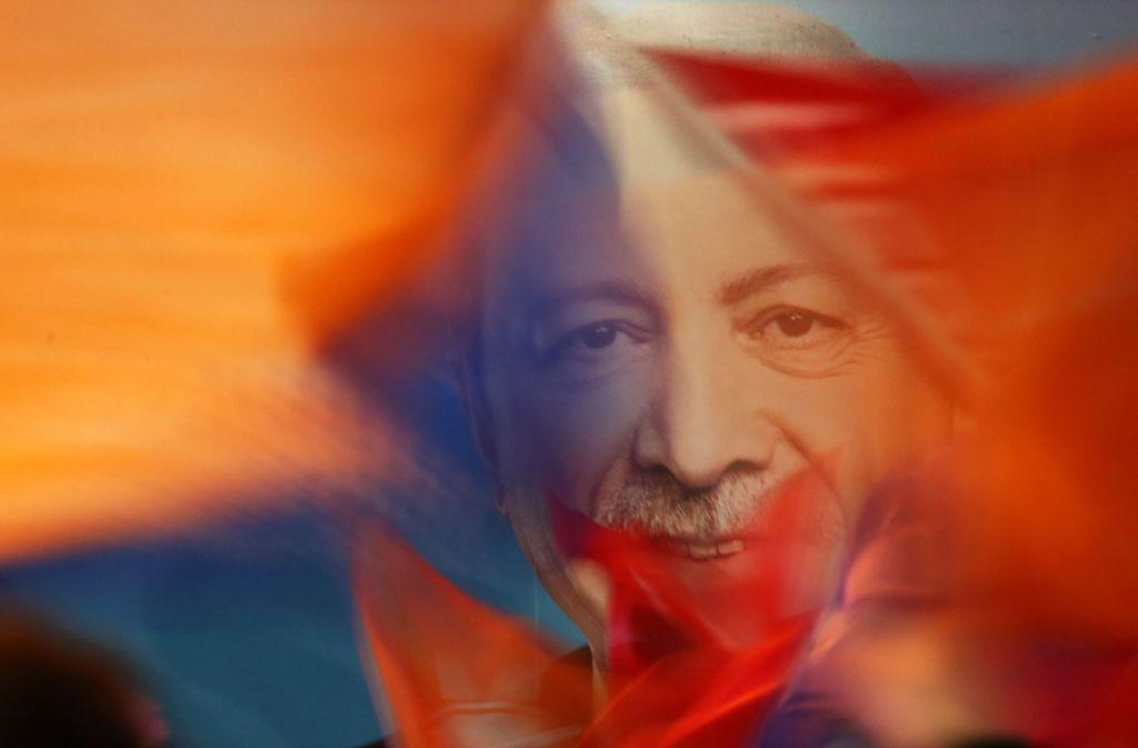 Anhänger schwenken nach der Wahl Fahnen mit dem Bild von Präsident Erdogan Foto: AP